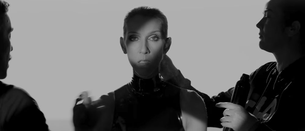 Celine Dion staring at the camera in front of a white backdrop
