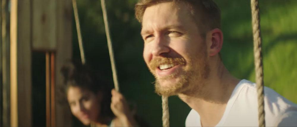 Calvin Harris sitting on a swing smiling alongside Jessie Reyez