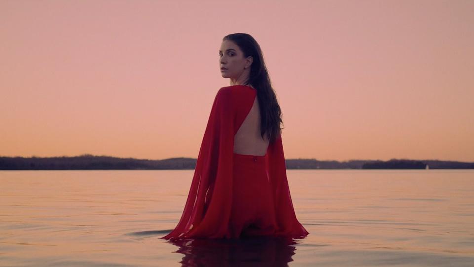 Woman in red dress waist deep in water under peach sunset skies
