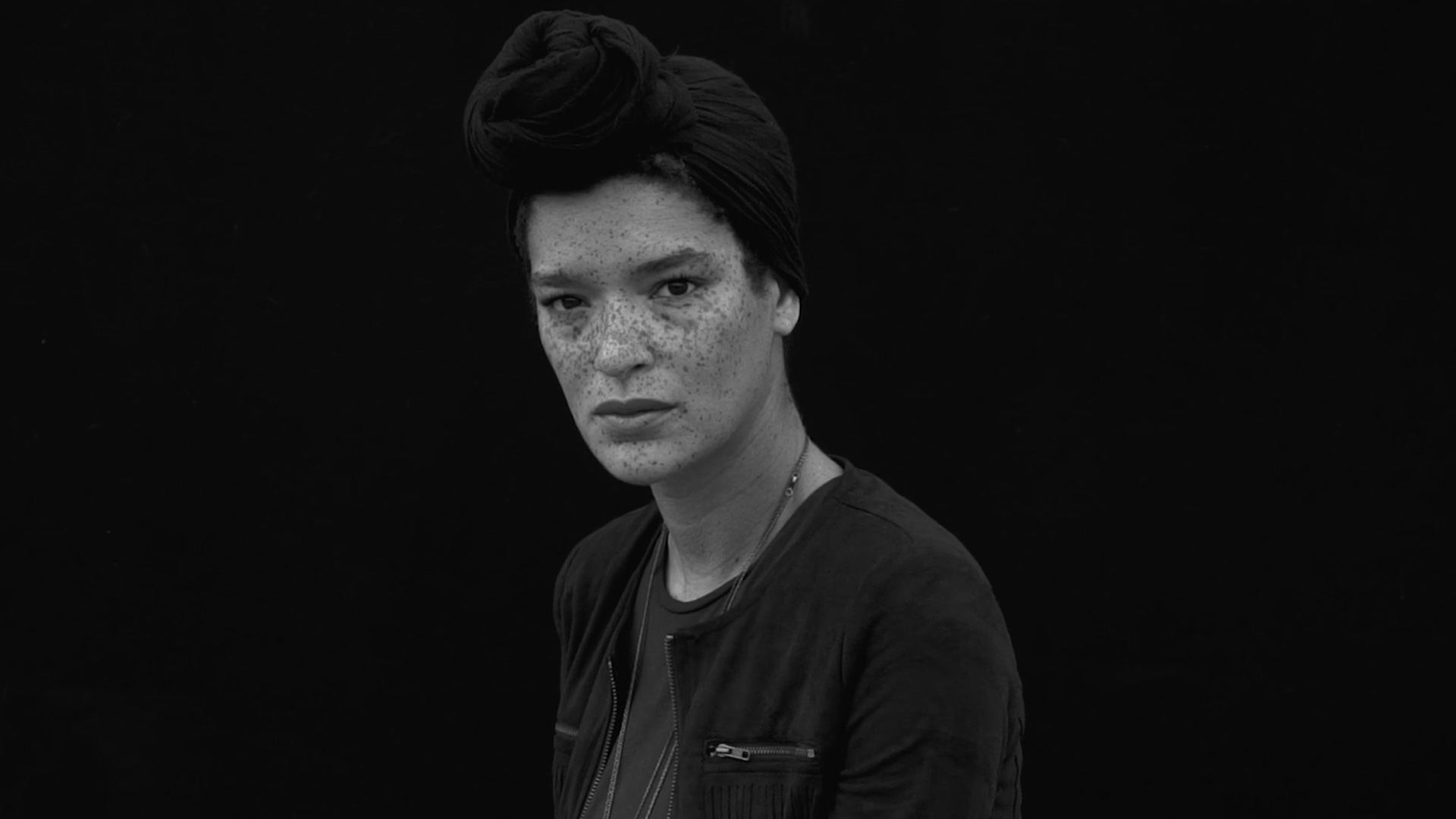 Black and white image of a woman with freckles gazing into the camera