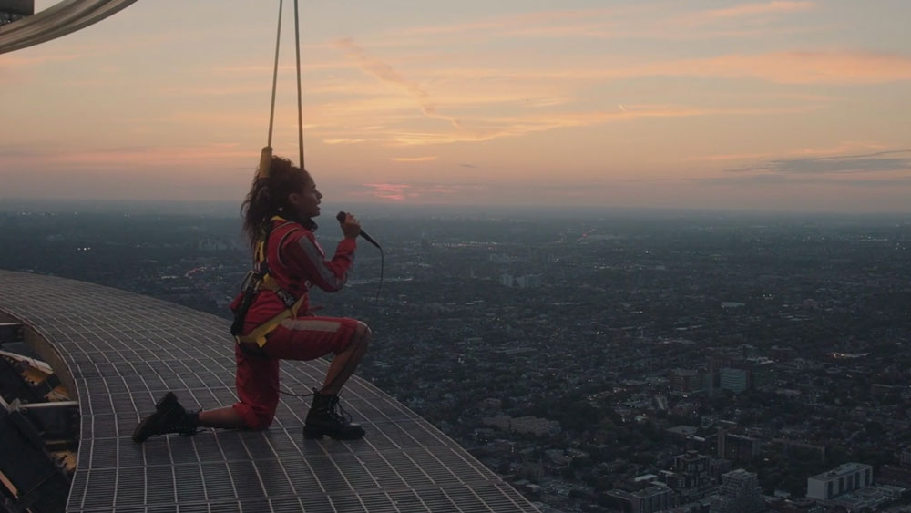 Jessie Reyez singing on top of the CN tower at dusk