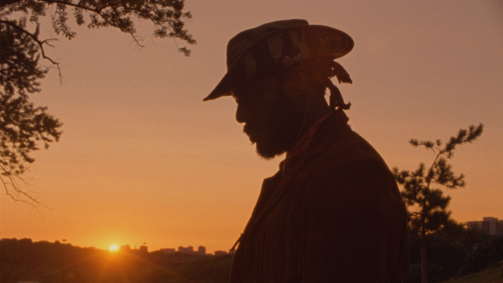 Man in hat in front of sunset sky.