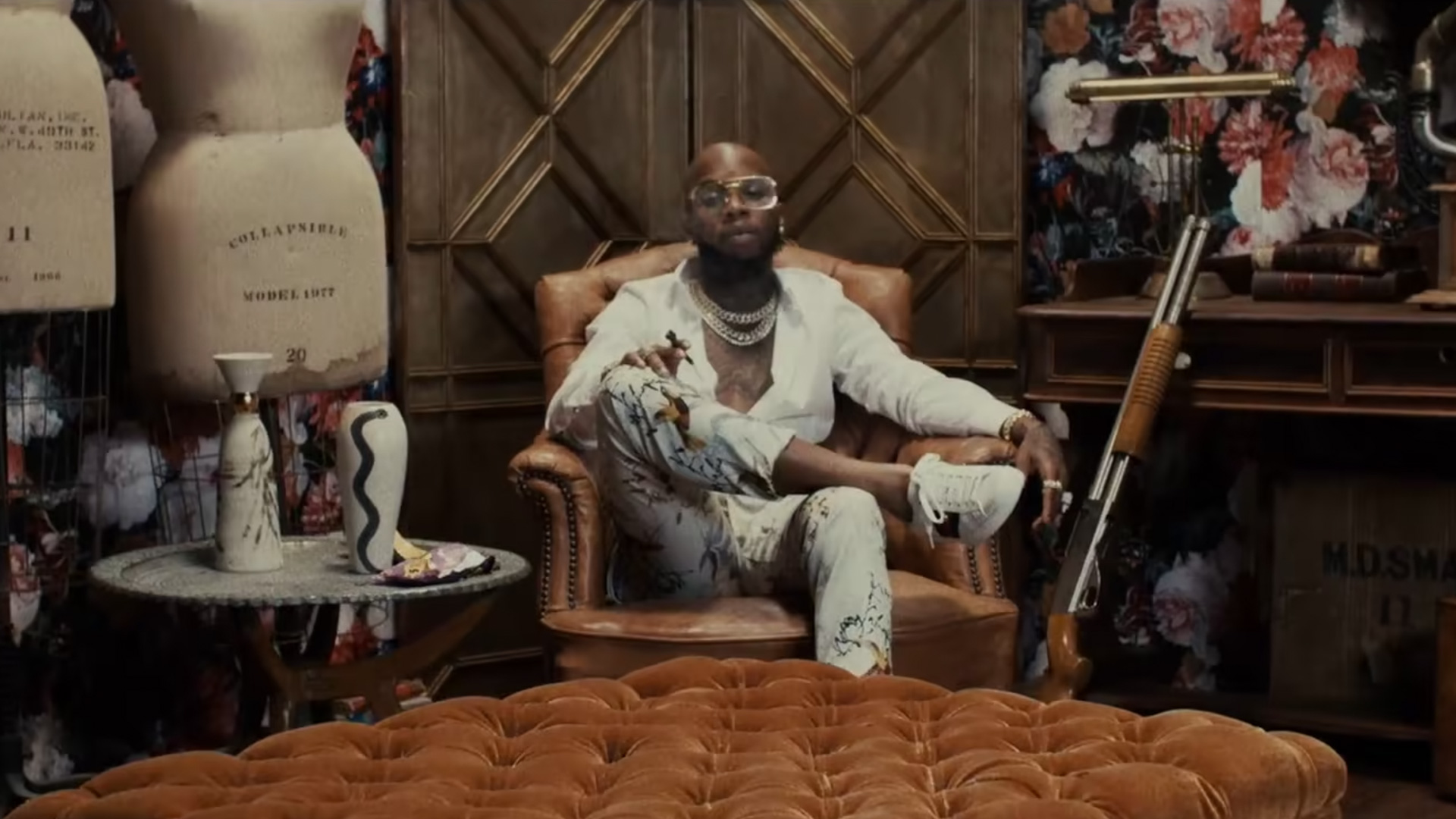 Man sitting on a leather chair next to fashion mannequins and a gun