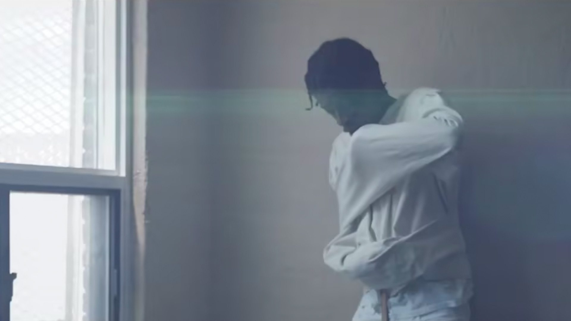 Man in straight jacket inside a building