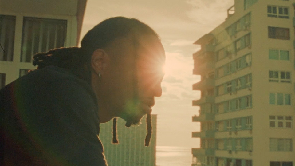 Hip Hop duo, 88 Glam, on a balcony looking out in Cuba with sun and skyscrapers behind them