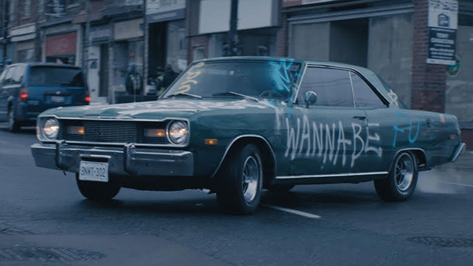 """Old car with """"Wannabe"""" spray painted on the door, sitting in the middle of road"""