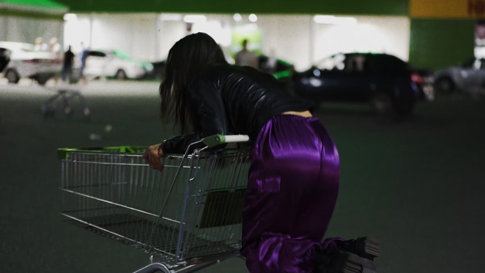Person riding on the back of a shopping cart in a parking lot at night