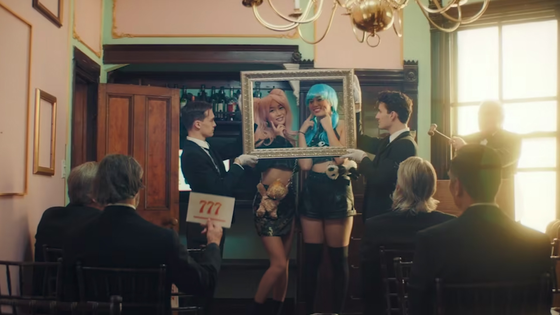 People in front of a room with colored wigs posing inside a gold picture frame
