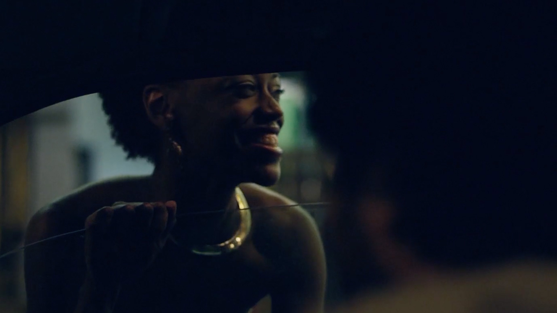 Woman smiling through a car window at night