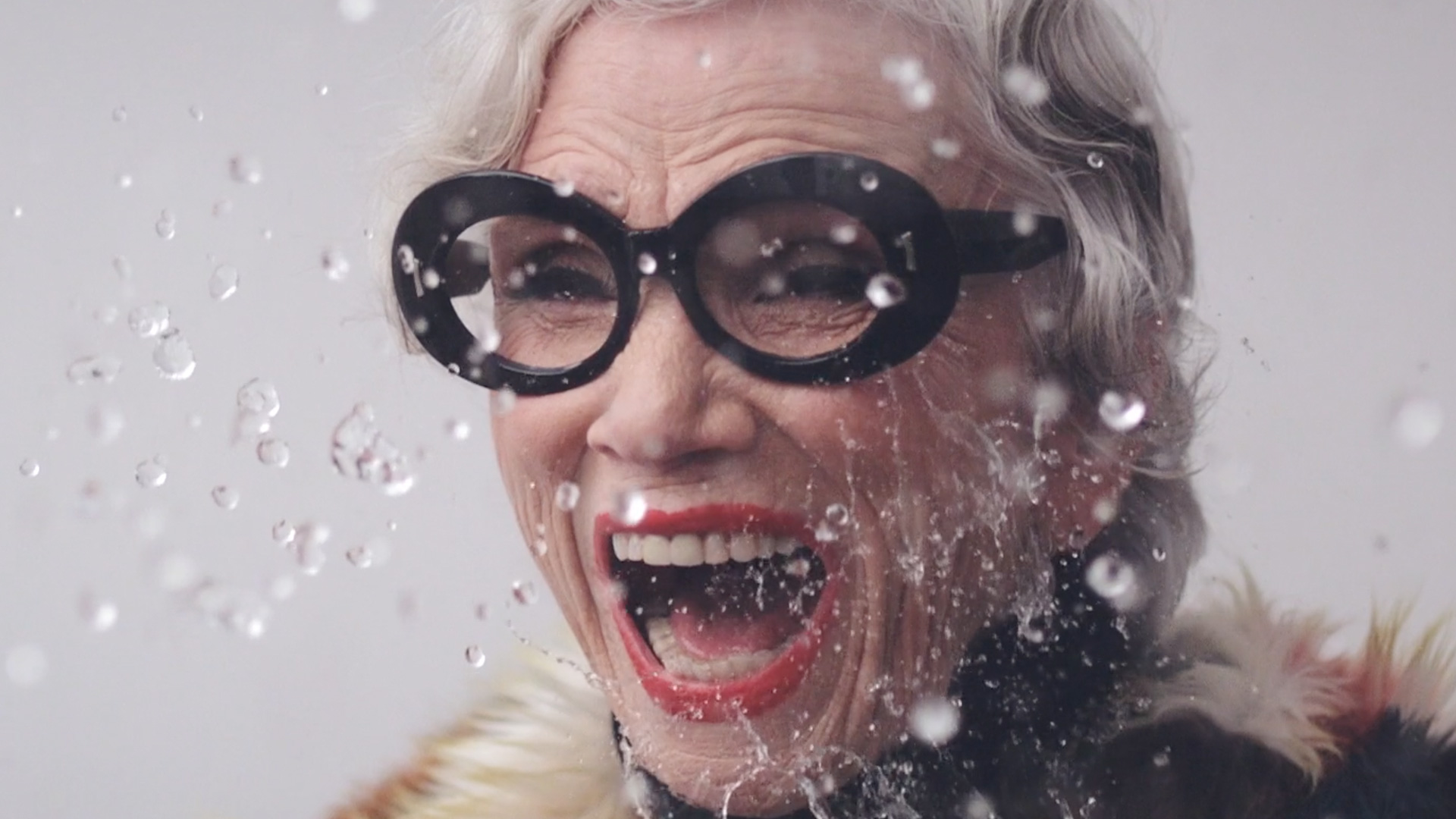 Lady with black glasses smiling with joy