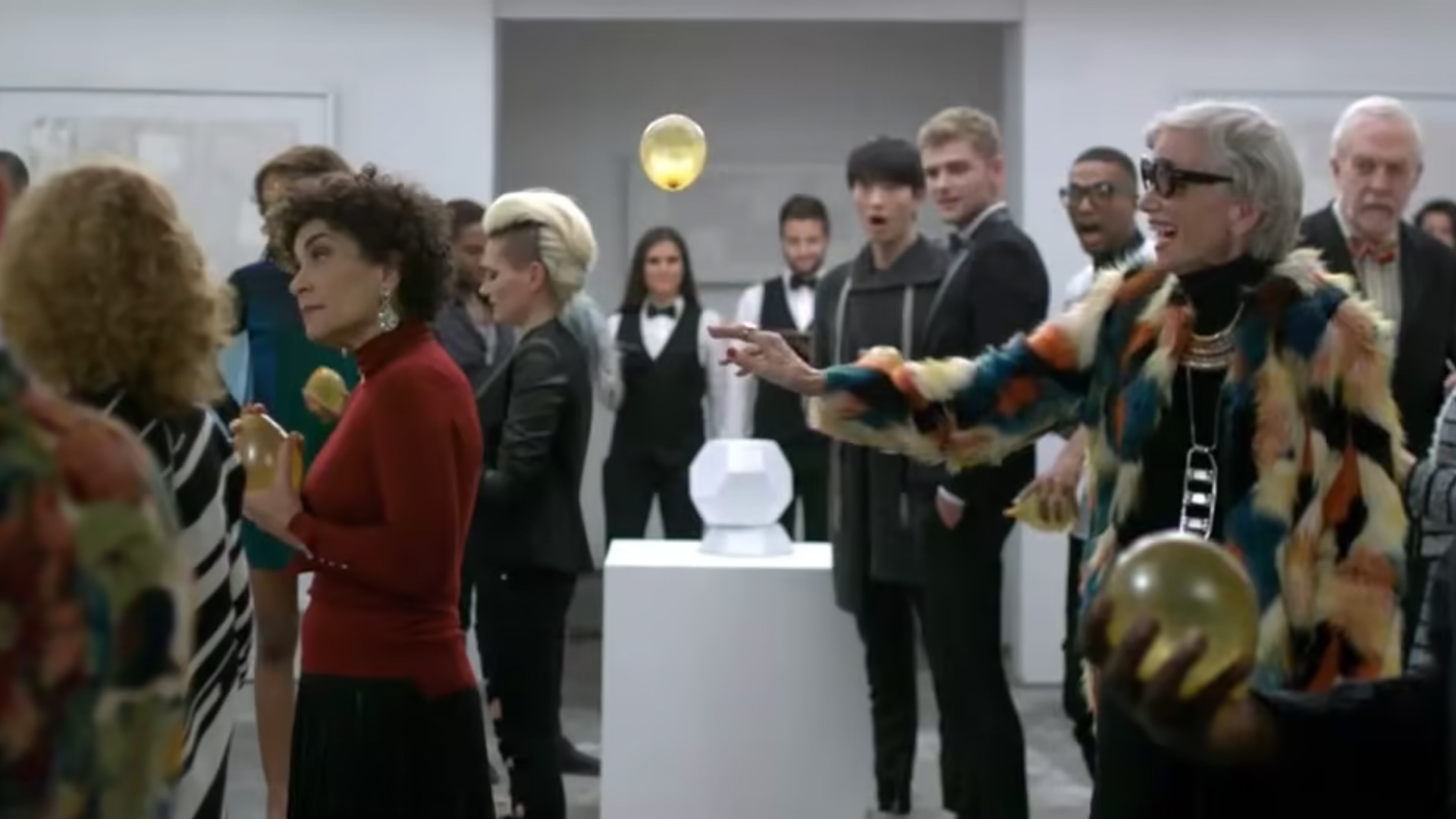 People at a gallery event with a woman holding a yellow balloon
