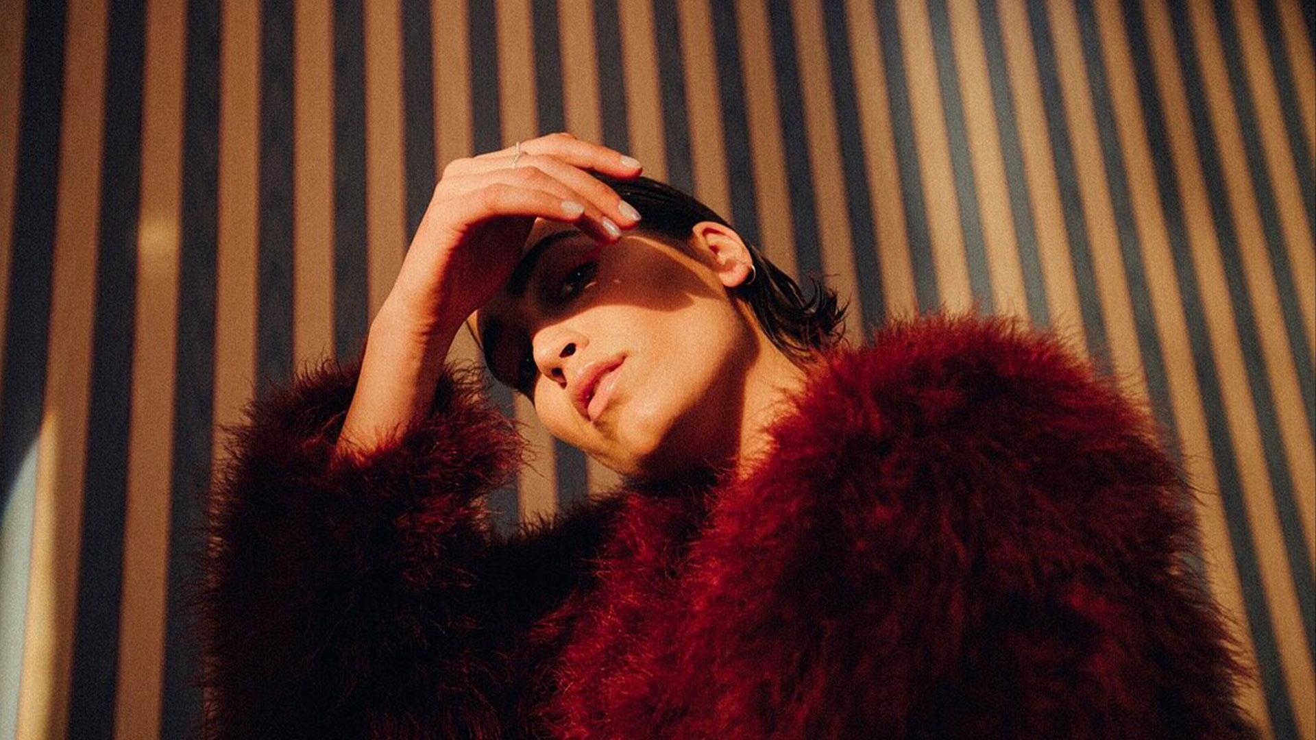 Woman in red fur coat in sunlit area.