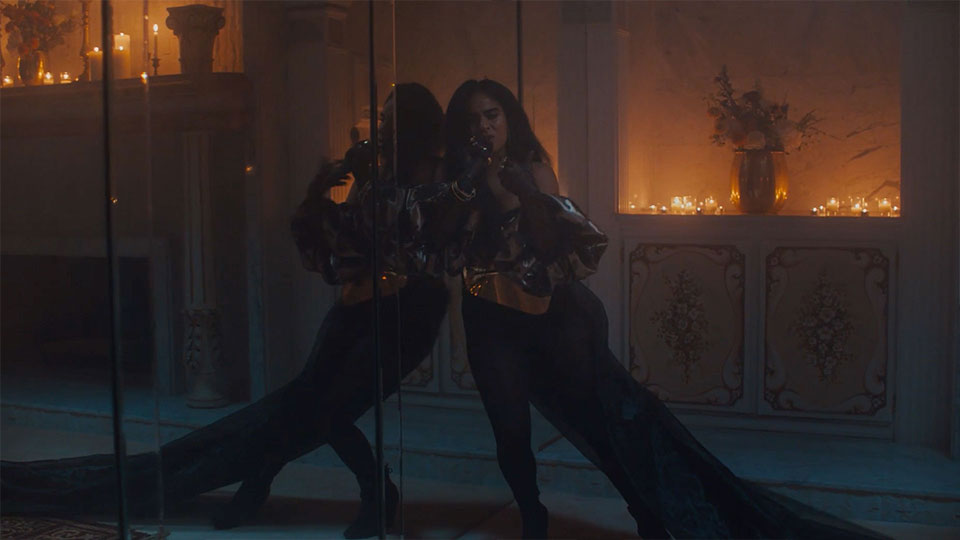 Jessie Reyez leaning and singing against a mirror.