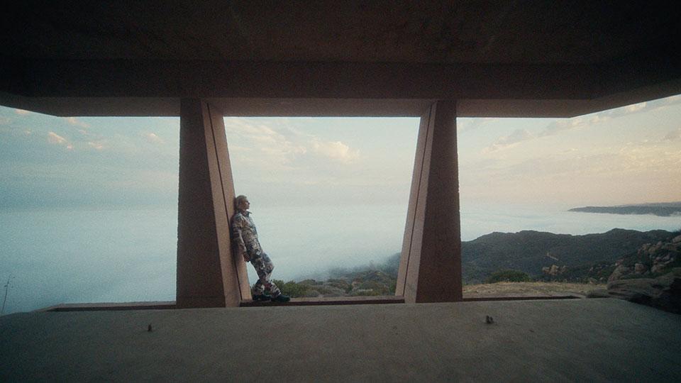 Man standing against a column against a cloudy mountainous background.