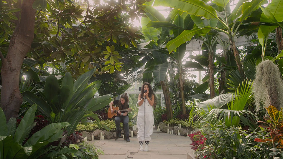 Jessie singing in a atrium full of lush plants