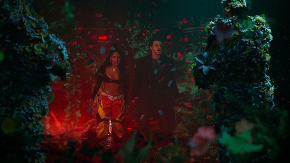 Jessie Reyez & grandson in a red lit room surrounded by an explosion of flowers and soldiers.