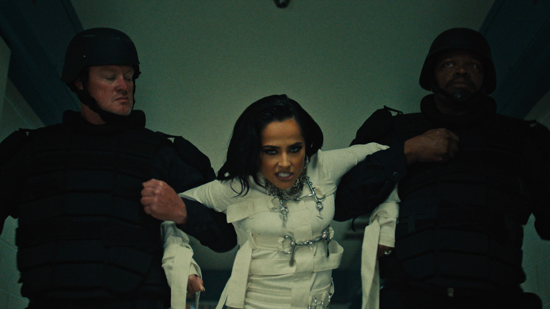 Woman in white being dragged down a hallway by two bodyguards.