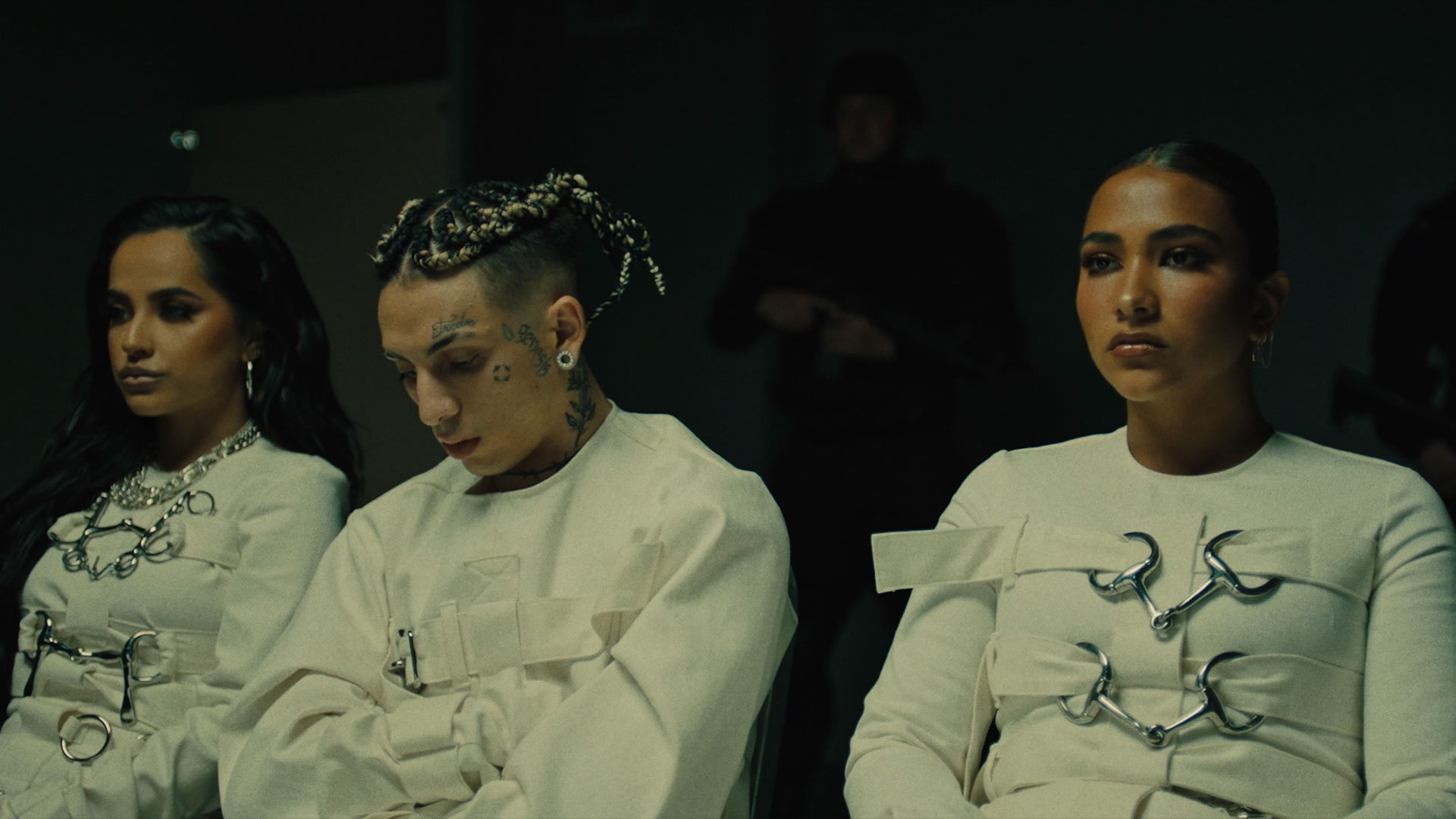 3 individuals in white sitting in an interrogation room.