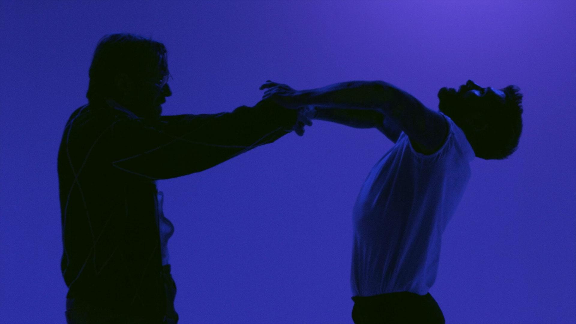 Two men holding hands against a blue/purple backdrop.
