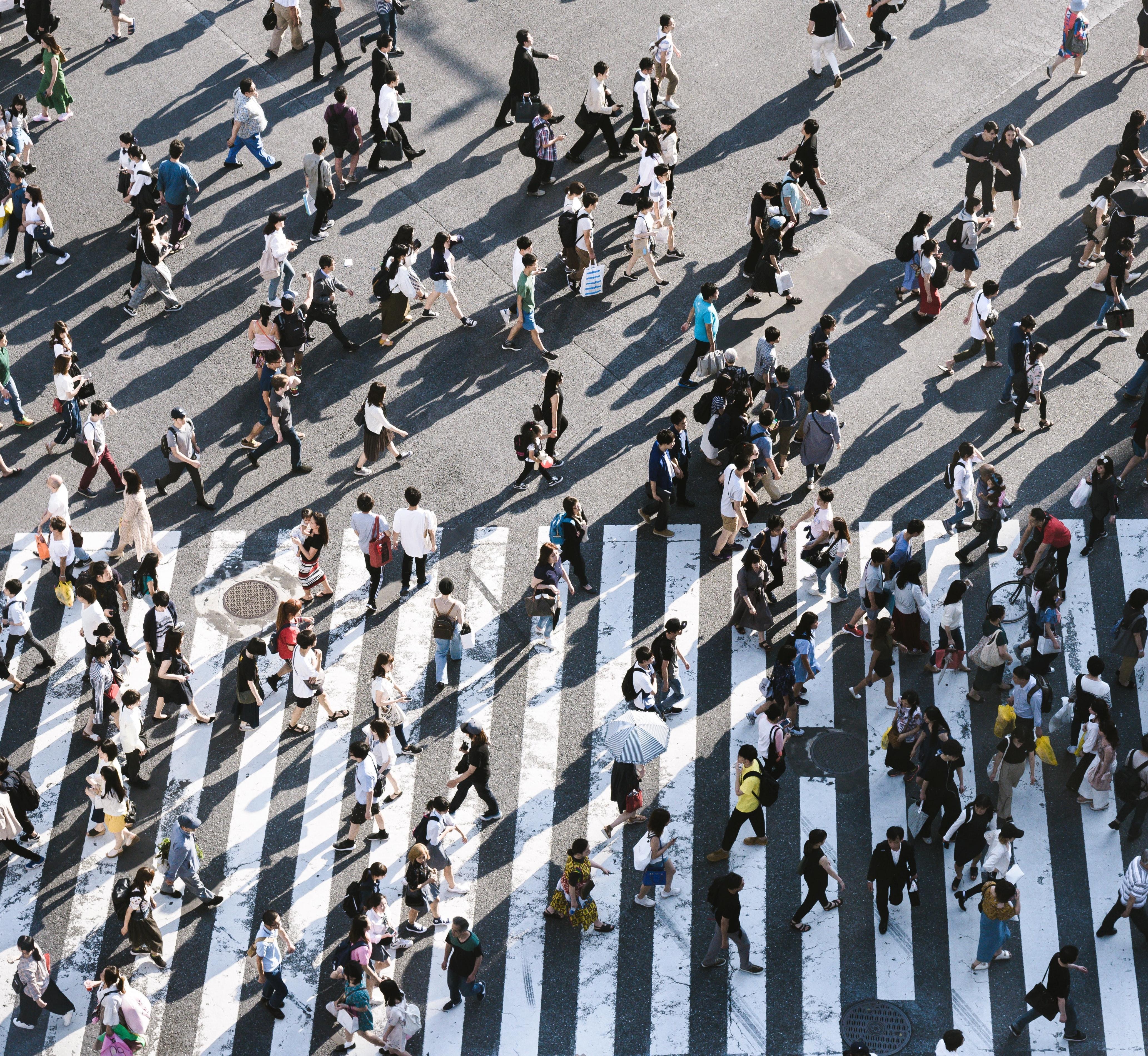 Swarms of people crossing sidewalk
