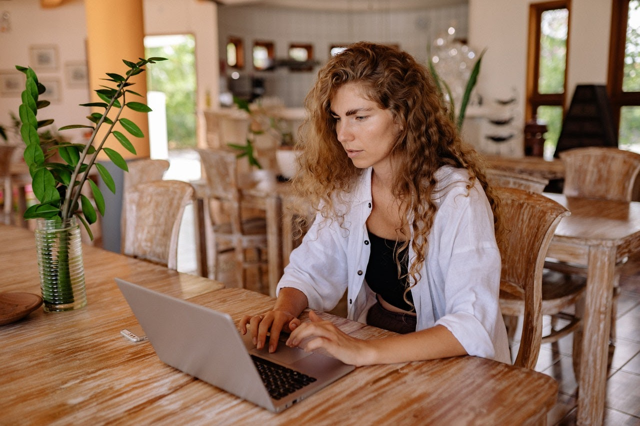 a woman sits at her laptop monetizing her blog