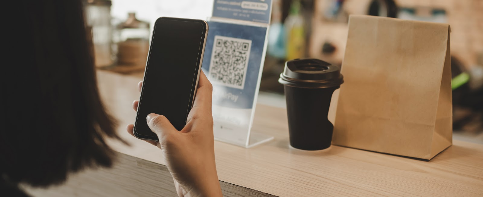 A woman scanning a qr code at the counter to pay for the take-away coffee and food