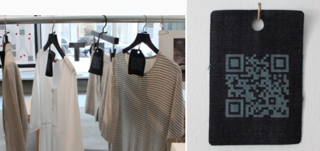 t-shirts on hangers with big QR code material tags on them