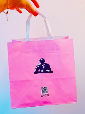 a qr code on a pink paper take away bag
