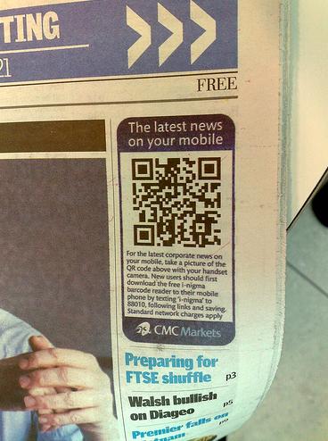 CMC markets qr code advertisement in a free newspaper
