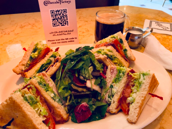 club sandwich and a qr code menu display at the cheesecake factory cafe