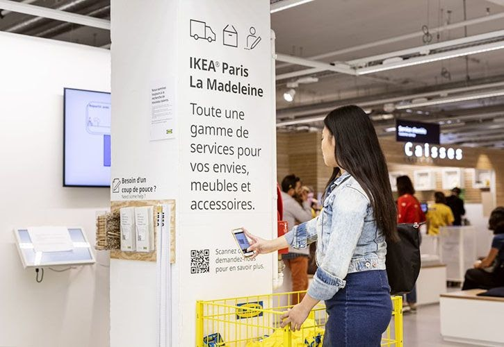 a woman scanning a QR code with a phone camera in the IKEA shop