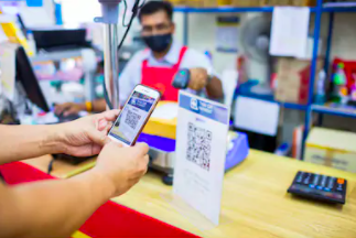 Hands scanning a qr code at register at a postal office