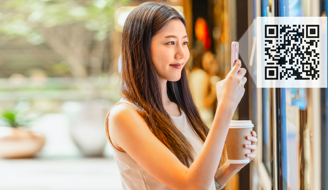 Asian young woman hand using smart mobile phone scanning QR code while colding coffee