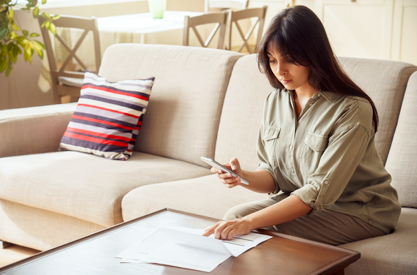 lady sitting on a sofa looking through documents and holding a phone