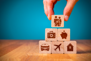 A hand adding a wooden block with a family symbol to other wooden blocks