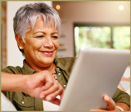 AN old happy lady holding an ipad searching the web