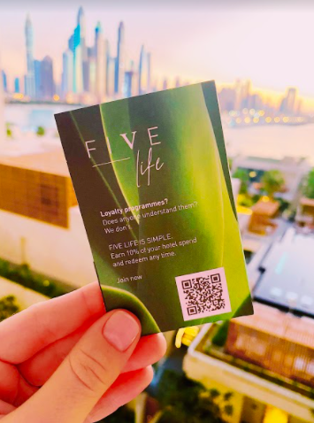 A hand holding a paper card holder with QR code loyalty program for a hotel in Dubai
