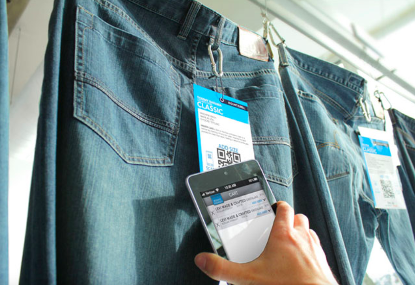 hand on mobile scanning QR code on jeans tag