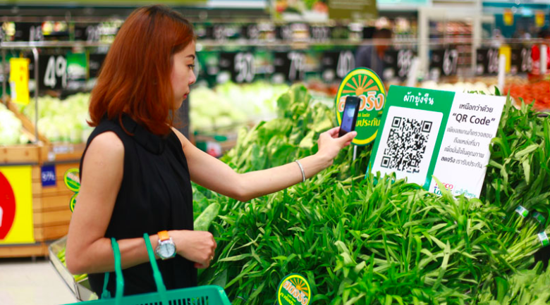 Asian lady scans QR code with mobile phone in vegetable aisle of grocery store