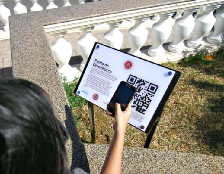 girl scans QR code on public park sign