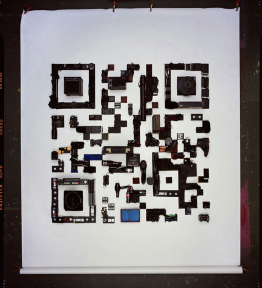 qr code made of bottles, boots, cameras, power tools by david sykes