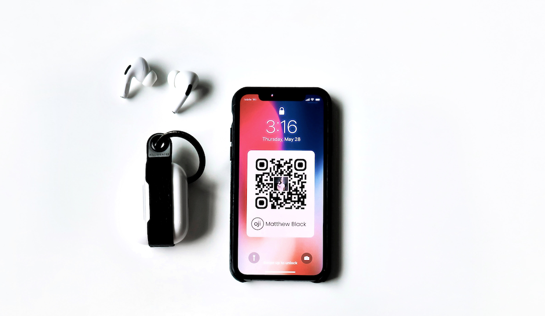 iPhone with a qr code on screen next to earbuds