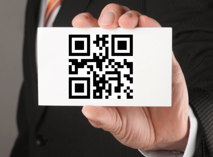 a hand holding a business card with a qr code