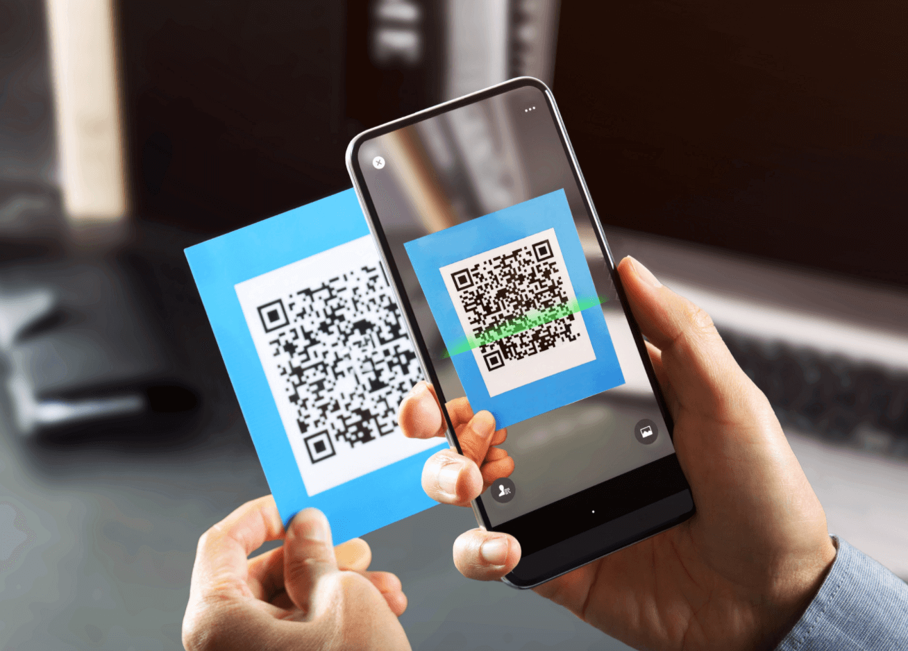 A hand with a phone scanning a printed QR code