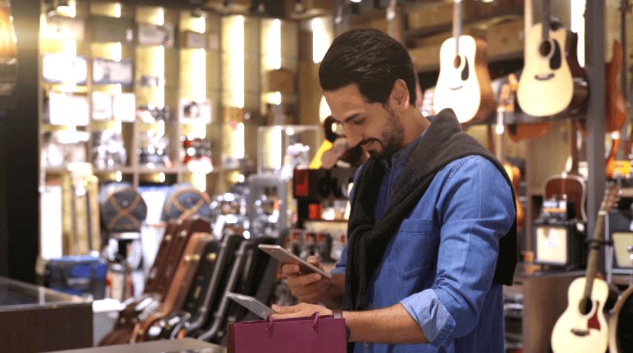 man scanning a qr code in a guitar store
