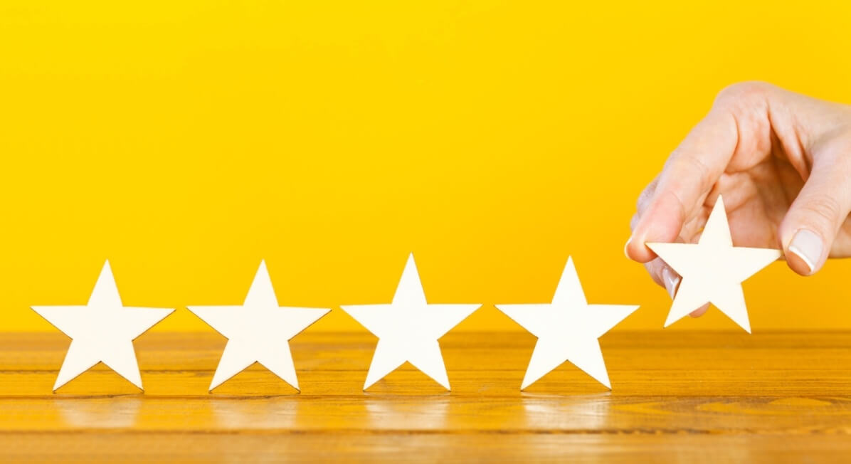 Five white stars on the table on yellow bright background