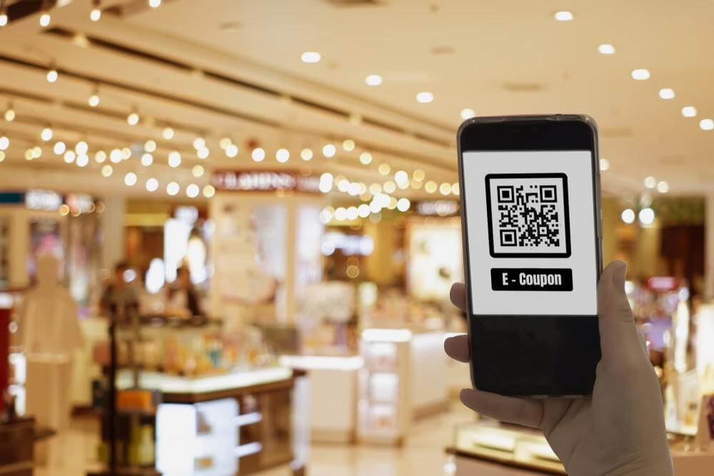 A phone with a QR code coupon and a bright store at the background