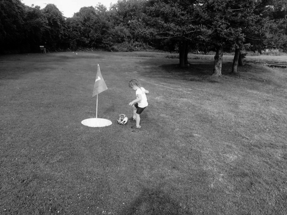 Kid kicking soccer ball into a foot golf hole