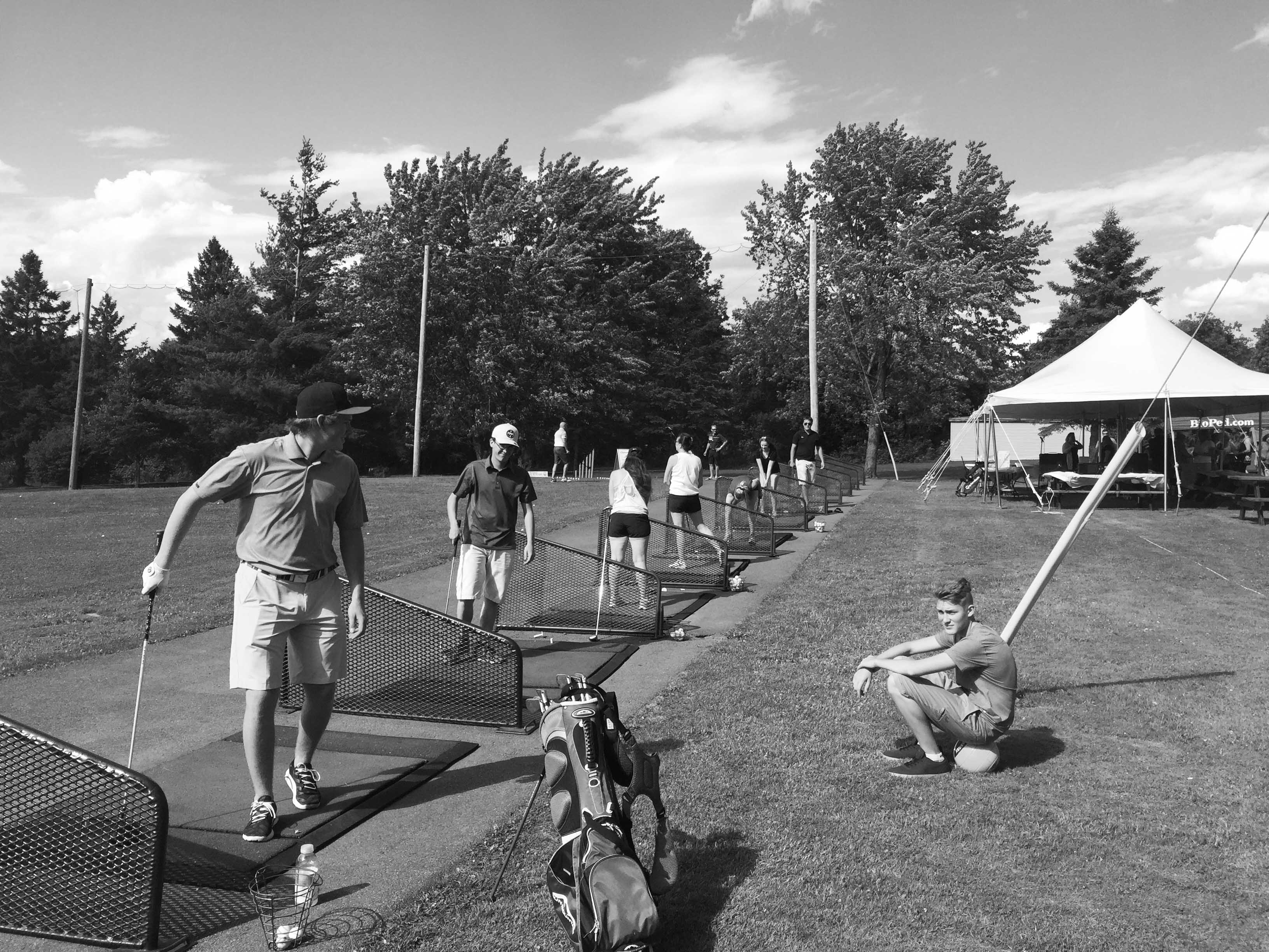 Multiple people at a driving range