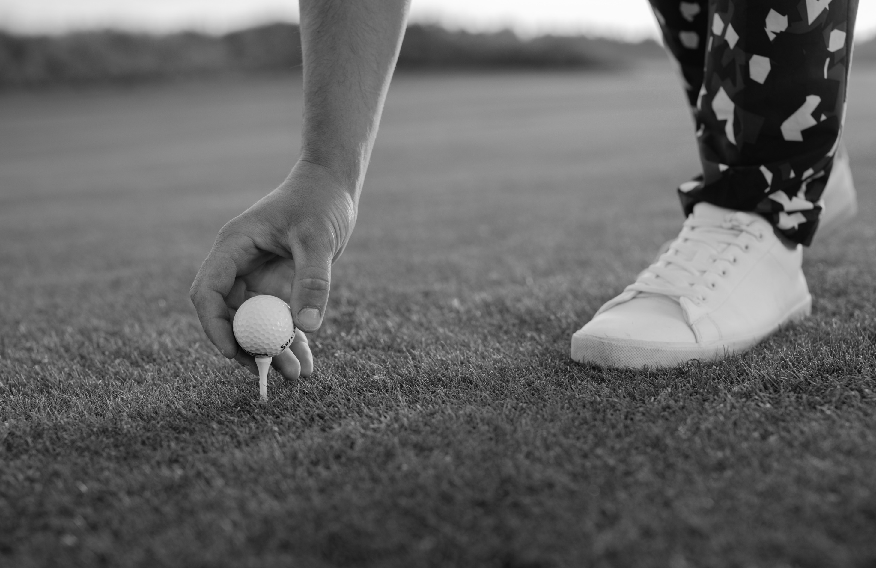 Close-up photo of person placing golf ball on golf tee